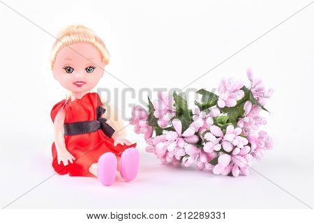 Baby doll and pink flowers. Cute little doll in red dress with pink bouquet of flowers sitting over white background. Holiday and gift concept.