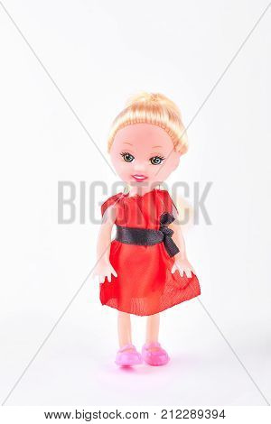 Doll in red dress on white background. Beautiful smiling baby doll with blond hair isolated on white background. Cute gift for child.