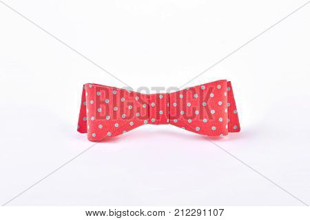 Red dotted bow tie on white background. Red bow for hair with blue spots. Trendy hair accessory.