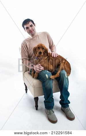 Fair skinned young man seated on chair smiling with his Golden Retriever puppy dog on lap.