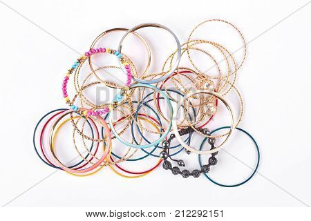 Collection of stylish bracelets, top view. Stack of different wrist bands for women, white background. Female bangles on sale.