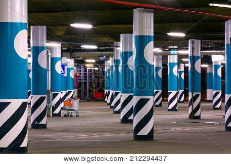 The shopping trolley is among the round blue columns on the asphalt parking lot neon lights in dark industrial building modern public construction. Empty shopping center parking at night.