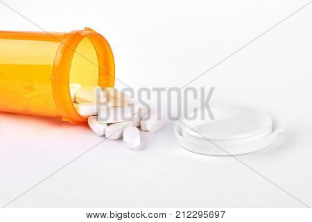 White pills spilled from pills bottle. Pills and medicine container lying on white background.