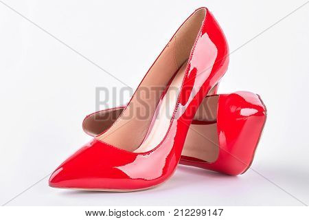 Fashion design high heels for woman. Female red leather stiletto over white background. Woman fashion footwear.