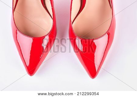 Woman new red lacquered shoes. Female red leather shoes isolated on white background. Elegant woman shoes on sale.