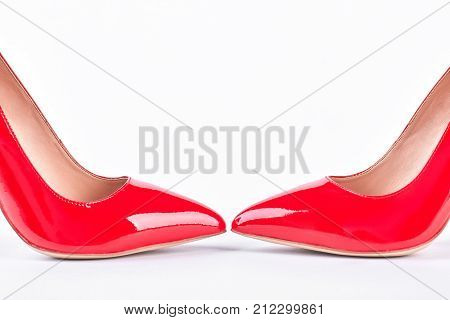 Pair of red glamour high heels. Female leather red shoes on high heels isolated on white background. Woman fashion and style.