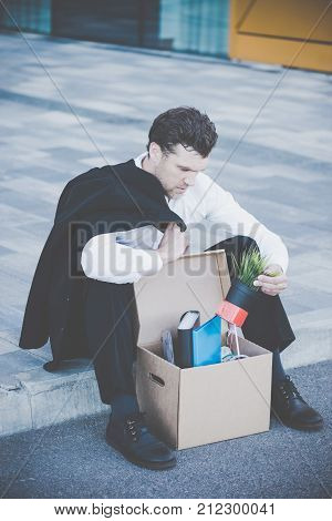 Fired business man sitting frustrated and upset on the street near office building with box of his belongings. He lost work