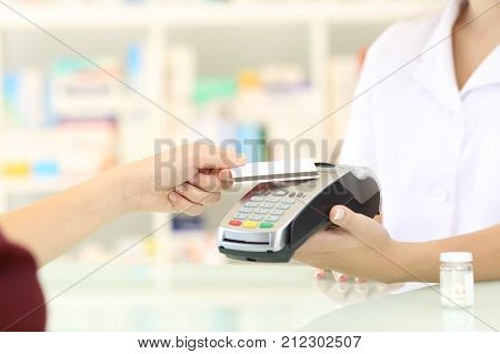 Customer Paying With Credit Card Reader In A Pharmacy