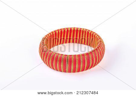 Female elegant bracelet on white background. Beautiful red and gold bangle over white background. Woman glamour hand accessory.