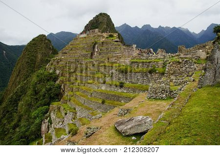 View over the steep terraces at the back side of the Machu Picchu Inca ruins in the Peruvian Andes.