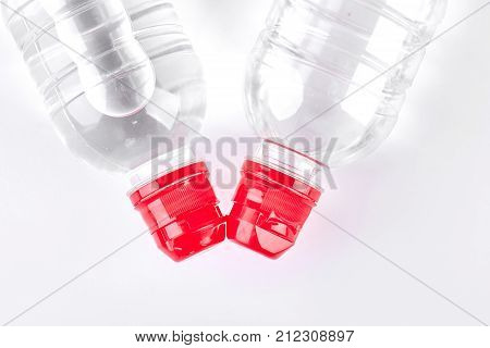 Bottles of water, top view. Two plastic bottles of water with red cap isolated on white background, top view. Natural water and healthy lifestyle.