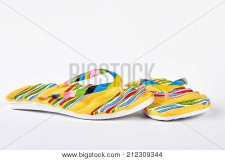 Woman fashion design flip flops. Yellow striped flip flops on white background. Summer fashion fotwear on sale.