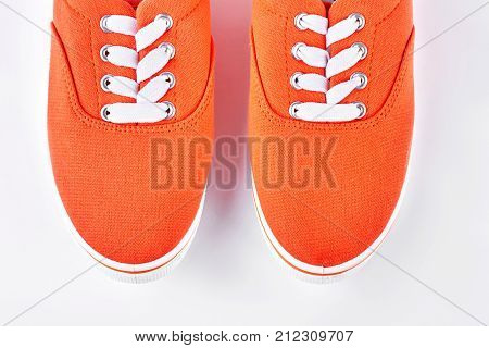 Pair of orange sneakers close up. Female new colored gumshoes isolated on white background. Woman trendy footwear.