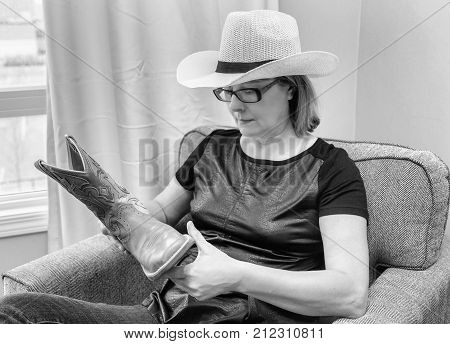 horizontal black and white image of a caucasian woman wearing a white cowboy hat sitting in a chair holding a cowboy boot and looking at it.