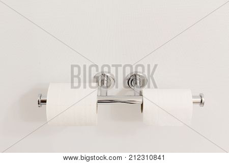 horizontal image of two rolls of toilet paper hanging on a double stainless steel toilet paper holder on a white wall.