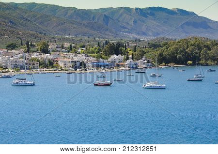 boats anchored in the waters of the saronic sea in front of the capital of the island of pores and bottom with the mountains of the island