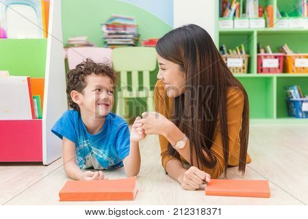 Young asian woman teacher teaching american kid in kindergarten classroom with happiness and relaxation. Education elementary school learning and people concept - teacher help school kids classroom.