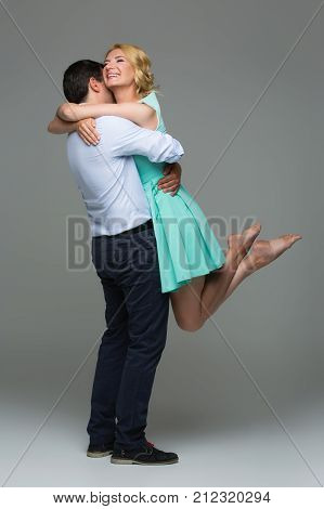 Beautiful young happy couple hugging. Blond woman in mint dress and handsome man in shirt and trousers standing on grey background. Valentine's day concept. People in love. Copy space.