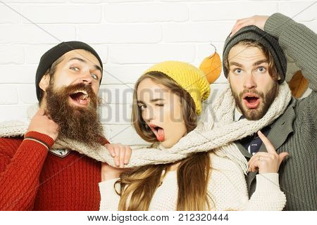 Girl and men at seasonal brick wall. Happy friends at autumn leaves in scarf and hat. Friendship happiness and relations. Men and woman happy family fashion. Season and autumn holiday.