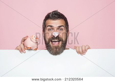 Sale and black friday shopping. Guy hold moneybox or piggy bank for savings. Crisis and loan. Bankruptcy and handout. Man with beard on happy face take credit.
