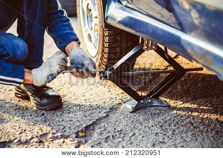 Jacking up a car to change a tyre after a roadside puncture with the hydraulic jack inserted under the bodywork raising the vehicle and the spare wheel balanced on the side.