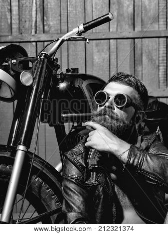 Bearded man hipster biker brutal male with beard and moustache in vintage sunglasses and leather jacket sits near motorcycle on wooden background