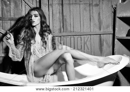 One beautiful sensual serious dreaming flirtatious young woman with long hair in blue knitted cloth sitting in white bath tub playing with soap foam indoor on wooden background horizontal picture
