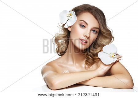 beautiful blond young woman with white orchid flowers. beauty studio shot isolated on white. copy space.