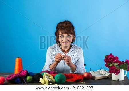 Old lady or grandmother with needle and yarn. Needlework knitting hobby. Granny character at Christmas eve womens day. Pension and retirement old age. Old woman knitting socks from colorful thread.