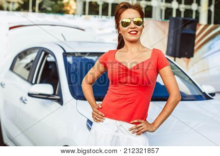 Sexy babe standing in front of tuned super-car