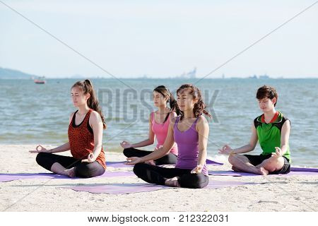 Group of young healthy asian people practicing yoga on the beach healthy lifestyles wellness well being