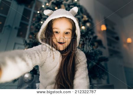 Shocked Little Girl Opening A Gift At Home In The Living Room