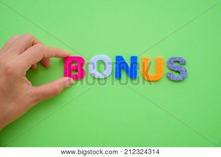 Abstract hand arrange BONUS alphabets word on green background. Business achievement concept.