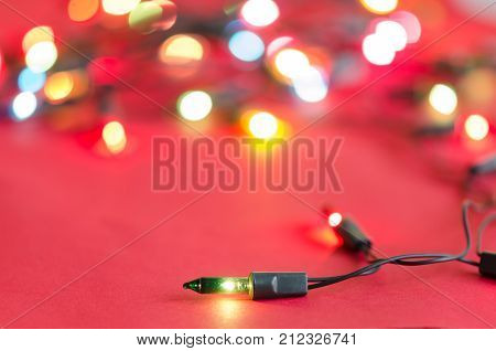 Xmas light bulbs on string in multi colours; blue yellow green pink & red on red velvet background with copy space & bokeh (blurry lights) for Christmas new year celebration (tree ornament concept)