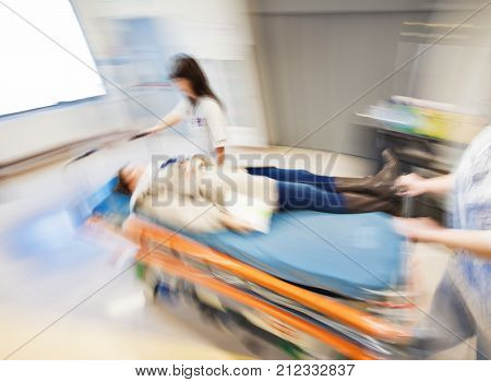 An emergency litter with patient, pushed fast through modern hospital corridor by two nurses. Panned, motion blurred picture.