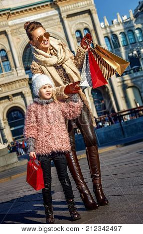 Rediscovering things everybody love in Milan. smiling modern mother and child travellers with shopping bags at Piazza del Duomo in Milan Italy pointing on something