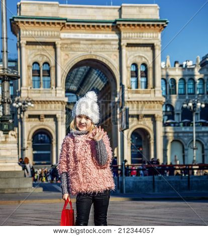 Rediscovering things everybody love in Milan. Full length portrait of happy modern girl with red shopping bag at Piazza del Duomo in Milan Italy handwaving