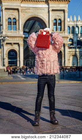 Rediscovering things everybody love in Milan. Full length portrait of modern girl in Milan Italy hiding behind red shopping bag