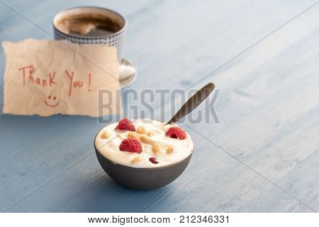 Yogurt with raspberry in a bowl - Healthy breakfast with yogurt and fresh raspberry fruits and a cup of coffee in background with a thank you message wrote on a piece of paper