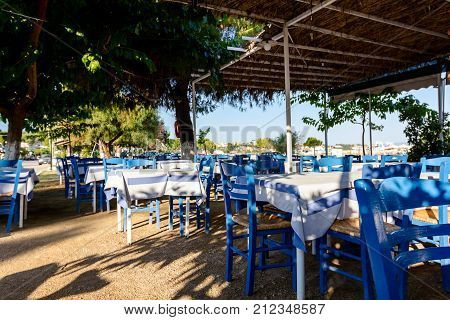 Chairs and tables in typical outdoor Greek tavern in morning sunlight with shadows on seashore.