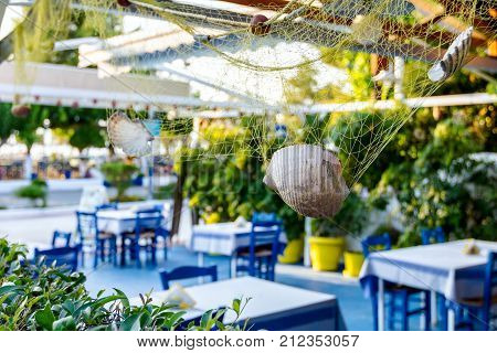 Abstract scene with sea shells in fishing net as decoration at traditional Greek tavern restaurant.