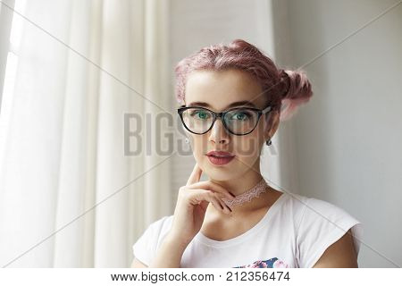 Low angle view of fashionable young European female in trendy cat eye glasses looking at camera with thoughtful expression on her pretty face making plans for day going to meet friends at cafe