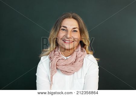 Positive human emotions and feelings. Portrait of beautiful cheerful middle aged woman with loose hair posing at blank studio wall looking at camera with joyful smile expressing joy and happiness