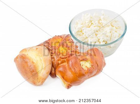 Pile of the different baked pies stuffed with cottage cheese against of glass bowl of cottage cheese on a white background