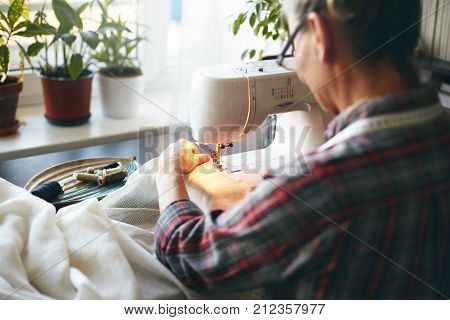 Back view of unrecognizable elderly needlewoman in plaid shirt sewing kitchen curtains using stitching machine. Senior female dressmaker spending early morning repairing or altering clothing item