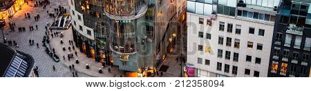 VIENNA, AUSTRIA - FEBRUARY 9, 2016: Crowd of people at the Stephansplatz in Vienna, Austria. Aerial night view of famous landmark with many shops, restaurants, bars and modern buildings