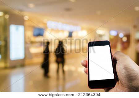 blank screen mobile phone in hand with blurred image of people shopping at shopping mall background internet connection communication technology social network and shopping online concept