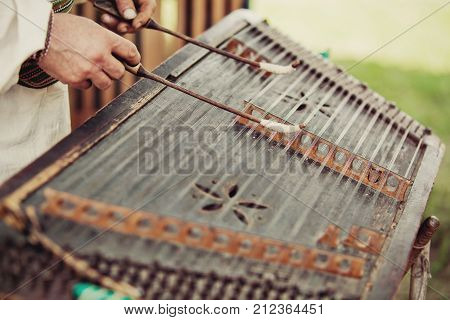 Ukrainian traditional music string instrument tsymbaly. Man wearing traditional clothes playing folk Ukrainian music. Close view