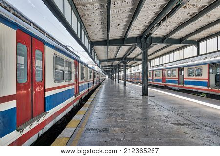 Interior shot of Haydarpasha Railway Terminal featuring metal truss and two colored stopped trains Kadikoy Istanbul Turkey built 1909 and closed in 2013 due to the rehabilitation of Marmaray line