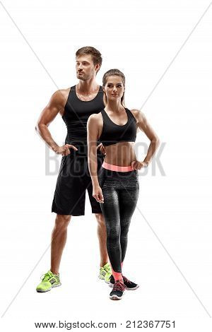 Sport, fitness, workout concept. Fit couple, strong muscular man and slim woman posing on a white background. A man and a woman in sportswear